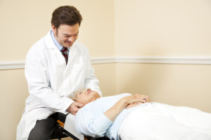 Chiropractor adjusting the neck of an elderly female patient
